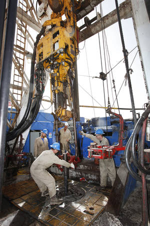 Photo - Floorman Justin Stanfill, Paul Tabarez and William Reed break a joint in drill pipe that is being pulled on a SandRidge oil drilling rig near Medford, in 2012. <strong>David McDaniel - The Oklahoman</strong>