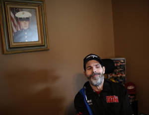 Photo - Scott Bates smiles as he talks about designing NASCAR car decals. in Muskogee, Okla., Tuesday, Oct. 29, 2013. His U.S. Marine portrait hangs on the wall. Photo by Sarah Phipps, The Oklahoman