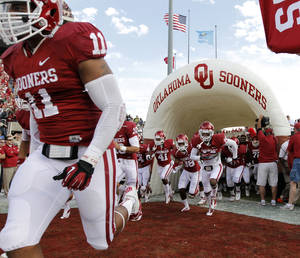 Photo - Oklahoma's R.J. Washington (11) leads the team on the field during the college football game between the University of Oklahoma Sooners (OU) and Baylor University Bears (BU) at Gaylord Family - Oklahoma Memorial Stadium on Saturday, Nov. 10, 2012, in Norman, Okla.  Photo by Chris Landsberger, The Oklahoman