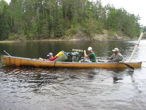Photo - Declan Lawson, Tyler Cotner and Dean Kelley turn around the 23-foot canoe with all of their gear. Most of the Boundary Waters Canoe Area Wilderness in northern Minnesota can only be reached by hiking or by paddling and portage. Photo by Jim Lawson
