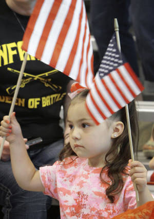 Photo - Above: Gabriella Garcia, 4, of Tulsa, waves a flag at the ceremony.