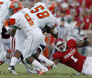 Photo - Oklahoma's Tony Jefferson (1) tries to bring down Florida A&M's Eddie Rocker (9) during the college football game between the University of Oklahoma Sooners (OU) and Florida A&M Rattlers at Gaylord Family-Oklahoma Memorial Stadium in Norman, Okla., Saturday, Sept. 8, 2012. Photo by Bryan Terry, The Oklahoman