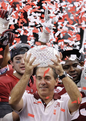 Photo - FILE- In this Jan. 9, 2012, file photo, Alabama head coach Nick Saban holds up the trophy as he celebrates with his team after defeating LSU 21-0 in the BCS national championship NCAA college football game in New Orleans. The D word - as in dynasty - is off-limits around Alabama. But if Saban's Crimson Tide can beat No. 1 Notre Dame to become the first team to win consecutive BCS championships and three national titles in four years, Alabama will lay claim to one of the sport's great runs. (AP Photo/Gerald Herbert, File) ORG XMIT: NY162