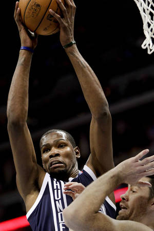 Photo - The Thunder's Kevin Durant grabs a rebound during Thursday night's matchup against the Nuggets. AP photo