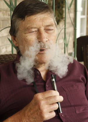 Photo - Bob Clark demonstrates his e-cigarette that he is using to quit smoking at his home in Edmond. Clark has smoked for the past 50 years but hopes to quit this month. <strong>PAUL HELLSTERN</strong>