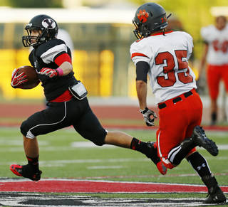 Yukon's Hunter Sconce (5) carries the ball past Norman's Logan Hill (35) during a high school football game between Norman and Yukon at Yukon High School in Yukon, Okla., Friday, Sept. 20, 2013. Photo by Nate Billings, The Oklahoman