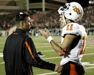 Head coach Mike Gundy talks with quarterback Zac Robinson during the second half of the college football game between the Oklahoma State University Cowboys (OSU) and the Texas Tech Red Raiders at Jones AT&T Stadium on Saturday, Nov. 8, 2008, in Lubbock, Tex. Texas Tech won 56-20. By Steve Sisney/The Oklahoman