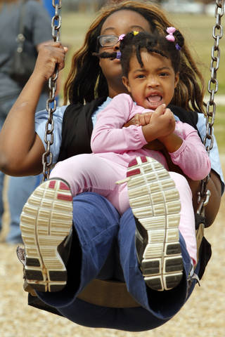 Jozette Masiah and daughter Talia, 3, swing Tuesday at Andrews Park in Norman.
