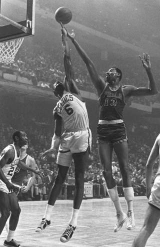 Boston Celtics basketball player Bill Russell (6) outreaches Philadelphia 76ers Wilt Chamberlain (13) to control a rebound in Boston in this Jan. 15, 1967 photo. Chamberlain, a center so big, agile and dominant that he forced basketball to change its rules and the only player to score 100 points in an NBA game, died Tuesday, Oct. 12, 1999 at 63.(AP Photo)