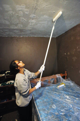 Casady High School junior Ayman Paracha, 16, paints a bedroom ceiling as students from Mercy School and Casady School help repair a home in northeast Oklahoma City on Monday.