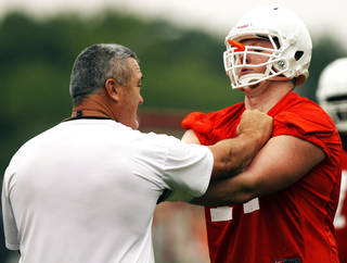 OKLAHOMA STATE UNIVERSITY / OSU COLLEGE FOOTBALL: Oklahoma State offensive line coach Joe Wickline gives instruction to lineman Parker Graham (right) during practice on August 2, 2013. Wickline is entering his 9th season at Oklahoma State. Photo by KT KING, The Oklahoman
