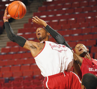 Cameron Clark (left) and Kyle Hardrick fight for a rebound in practice on Tuesday. Photo by Steve Sisney, The Oklahoman