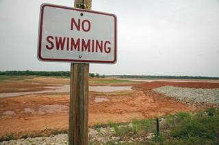 The no swimming sign currently seems rather obvious at Lake Stanley Draper, where the water level has been lowered since August to allow officials to make $46 million in renovations to equipment. Water is pumped to the lake from southeatern Oklahoma. It is stored at Lake Stanley Draper before being treated and distributed to Oklahoma City consumers.. STEVE SISNEY - THE OKLAHOMAN