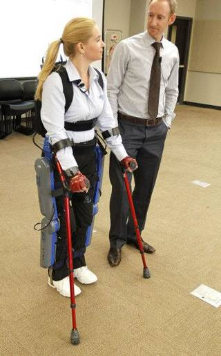 Agnes Fejerdy demonstrates the ReWalk gait system that returns mobility to spinal cord injury patients. Phil Astrachan, a physical therapist with Argo Medical Tehcnologies, stands nearby. PAUL HELLSTERN