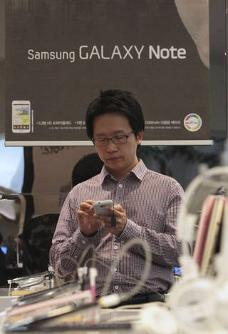 A shopper tries out Samsung Electronics' smart phone Galaxy on Friday at its showroom in Seoul, South Korea. AP Photo