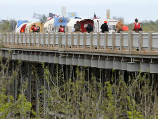 Wagons participating in the annual trail ride of the Sooner Teamsters and Trail Riders Association cross a bridge over the Canadian River Thursday as they make their way to Norman for a downtown parade on Saturday. PHOTO BY STEVE SISNEY, THE OKLAHOMAN STEVE SISNEY