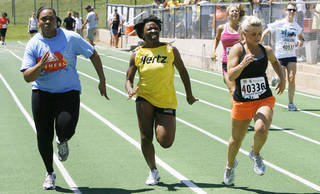 Jhavonne Pope with Farmers Insurance, left, Tasia Galbreath with Hertz, and Lacey Neuman with Chesapeake Energy, cross the finish line together.