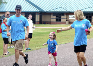 Riley Kahn, 3, and her parents Mike Kahn and Jill Kahn cross the finish line during the 1-mile fun run. PHOTOS BY TIFFANY M. POOLE, FOR THE OKLAHOMAN