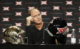 Baylor head coach Art Briles looks at a helmet while speaking to reporters during the NCAA college Big 12 Conference football media days in Dallas, Monday, July 21, 2014. (AP Photo/LM Otero)