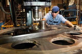 Mark Henley, a sheave technician at Gunnebo Johnson Corp., inspects a sheave's dimensions Friday at the company's factory, where parts are being produced for a mammoth floating crane called the Asian Hercules III. Photo by CORY YOUNG, Tulsa World