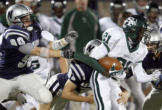 Edmond Santa Fe's Ryan Frazier tries to get past Edmond North's Nick Washburn, left, and Ragan Land during a high school football game at Wantland Stadium in Edmond, Okla., Friday, Oct. 29, 2010. Photo by Bryan Terry, The Oklahoman