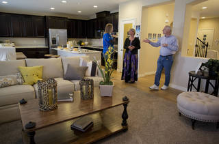 In this Friday, April 13, 2012 photo, Lennar Homes sales manager Joy Broddle, left, talks with Kelly, center, and Bill Noorish while standing in the living area of the main house of a model Next Gen home, in Las Vegas. The Noorishes, who moved to Las Vegas recently from Pensacola, Fla. and have a multigenerational home under construction, will be joined soon in by their 32-year-old son and his wife. Builders across the country are revamping home designs to meet the needs of a growing number of Americans who are now living with extended family. The number of so-called multi-generational households where adults are living with their elderly parents or grown children has jumped since the Great Recession forced Americans to rethink living on their own. (AP Photo/Julie Jacobson)