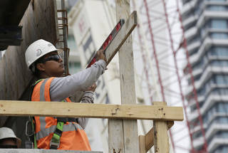 A construction worker works on the site of the SoMa at Brickell apartment building in downtown Miami. AP File Photo Lynne Sladky - AP