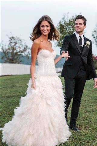 This Saturday, Sept. 29, 2012 image released by Michael Howard shows Kings of Leon bassist Jared Followill and model Martha Patterson at their wedding in Charlotte, Tenn. The couple married Saturday evening during a ceremony with friends and family at Front Porch Farms, about 40 miles outside Nashville. The 25-year-old Followill and 21-year-old Patterson were engaged last spring. Patterson wore a white dress with lace bodice and flowing feathered skirt by Monique Lhuillier and Followill wore black Gucci. (AP Photo/Michael Howard)