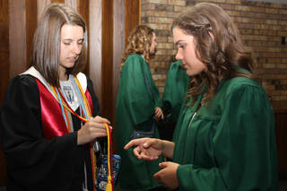Norman High School senior Elizabeth Waters, left, and Norman North senior Ashlyn Gardner decipher cord colors while waiting for baccalaureate services to begin at First Baptist Church. PHOTO BY LYNETTE LOBBAN, FOR THE OKLAHOMAN