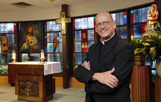The Rev. Ray Ackerman, pastor of St. John the Baptist Catholic Church, poses for a photo in one of the chapels at the Edmond church, 900 S Littler. The stained-glass windows in the background are from a former church building used by the parish. Photo by Jim Beckel, The Oklahoman Jim Beckel