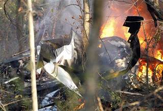 A small plane burns after crashing near a residential area in Owasso, Okla., Sunday Nov. 10, 2013. There was no immediate word on injuries or deaths as a result of the Sunday afternoon crash near the north Tulsa suburb. (AP Photo/Tulsa World, Mike Simons)