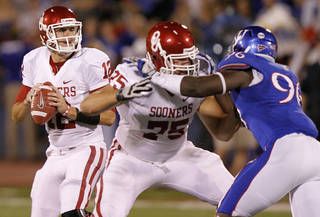 Oklahoma's Landry Jones (12) looks to pass the ball during the college football game between the University of Oklahoma Sooners (OU) and the University of Kansas Jayhawks (KU) on Saturday, Oct. 15, 2011. in Lawrence, Kan. Photo by Chris Landsberger, The Oklahoman