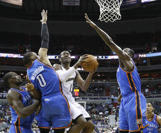 Washington Wizards' John Wall, center, shoots the ball on Oklahoma City Thunder's Serge Ibaka, of the Republic of Congo, left, Russell Westbrook (0) and Kendrick Perkins, right, during the first quarter of an NBA basketball game, Monday, March 14, 2011, in Washington. The Thunder won 116-89. (AP Photo/Luis M. Alvarez) ORG XMIT: DCLA107