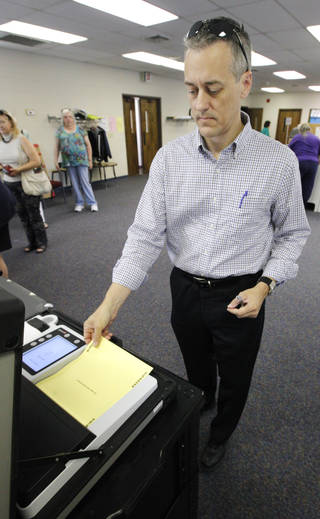 Wes Barnhill, of Oklahoma City, places his ballot into the voting machine Tuesday at precinct 012 in northwest Oklahoma City. Photo by Paul B. Southerland, The Oklahoman PAUL B. SOUTHERLAND