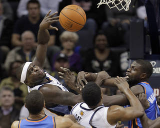 Memphis Grizzlies' Zach Randolph, top, and Rudy Gay fight for a rebound against Oklahoma City Thunder's Thabo Sefolosha, left, of Switzerland, and Nazr Mohammed, right, in the first half of an NBA basketball game Wednesday, Dec. 28, 2011, in Memphis, Tenn. (AP Photo/Lance Murphey) ORG XMIT: TNLM103