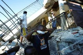 A man adjusts a piece of cloth over his face as he and others try to recover a friend's wife in Port-au-Prince, Haiti, Thursday, Jan. 14, 2010. (AP Photo/The Miami Herald, Carl Juste)
