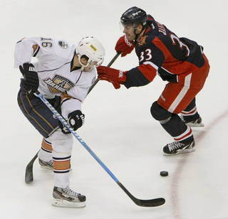Oklahoma City's Magnus Paajarvi (16) takes the puck past Grand Rapids' Doug Janik (33) during an AHL hockey game between the Oklahoma City Barons and the Grand Rapids Griffins at the Cox Convention Center in Oklahoma City, Saturday, March 24, 2012. Photo by Nate Billings, The Oklahoman