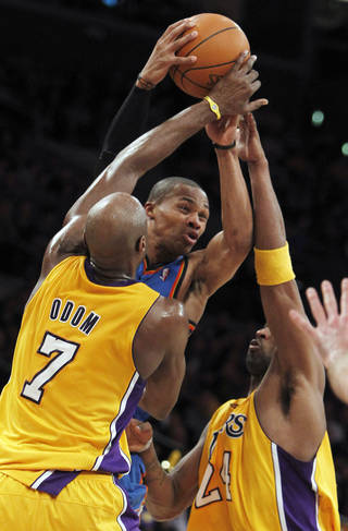 Oklahoma City Thunder guard Russell Westbrook, center, has his shot blocked as Los Angeles Lakers forward Lamar Odom (7) and guard Kobe Bryant, right, defend during the first half of an NBA basketball game Monday, Jan. 17, 2011, in Los Angeles. (AP Photo/Alex Gallardo) ORG XMIT: LAS206
