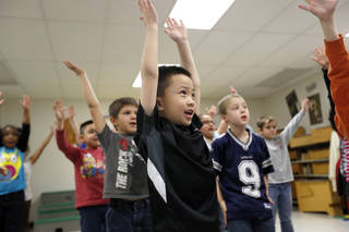 Right: First-grader Brian Bui practices during Christy Gosset's music class for a musical program at Western Oaks Elementary.