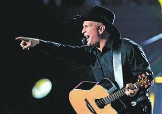 In this Jan. 25, 2008 file photo, country singer Garth Brooks performs during a charity concert in Los Angeles, to benefit the Southern California 2008 Fire Intervention Relief Effort (F.I.R.E). Brooks is going to be very busy in December. Brooks sold more than 140,000 tickets Saturday morning, Nov. 6, 2010, and his benefit concert for Nashville, Tenn., flood relief ballooned from one show to nine. (AP Photo/Mark J. Terrill, File)