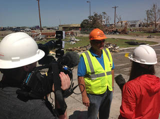 Greg Winters, superintendent of the Canadian Valley Technology Center, reviews storm recovery efforts with a TV news crew in early June at the tornado-damaged El Reno campus. PHOTO PROVIDED
