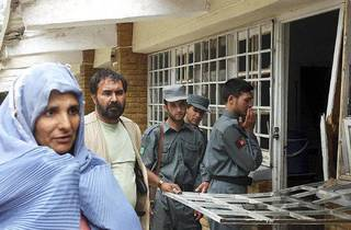 Afghan security officers stand at the door of a class room in which, a small explosion occurred at Herat university, south- western province of Afghanistan on Monday, July 3, 2006. Diane Guerrazzi was at Herat guest-lecturing in March when the lecture was interrupted by nearby suicide attacks. (AP Photo/Fraidoon Pooyaa)