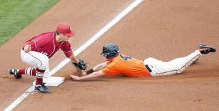 OSU's Saulyer Saxon, right, slides into third base as OU's Garrett Carey tries to tag him during Bedlam baseball action at the Chickasaw Bricktown Ballpark on Sunday. Photo by Sarah Phipps, The Oklahoman