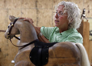 Jackie Wilson, of Edmond, places horse hair on one of her handmade wooden rocking horses. One of her horses went to Prince George. PHOTO BY SARAH PHIPPS, THE OKLAHOMAN.