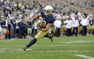 Notre Dame running back Cam McDaniel scores a touchdown against Michigan State during the second half of an NCAA college football game in South Bend, Ind., Saturday, Sept. 21, 2013. Notre Dame defeated Michigan State 17-13. (AP Photo/Michael Conroy) ORG XMIT: INMC114