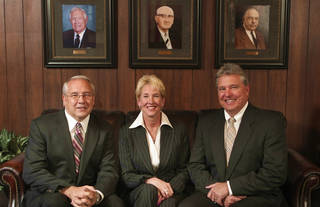 Siblings and co-owners of Yukon National Bank, Randy Wright, Carolyn Henthorn and Ray Wright sit in front of portraits of their ancestors who earlier ran the bank. Randy Wright is president and CEO of the bank. Henthorn is an executive vice president.