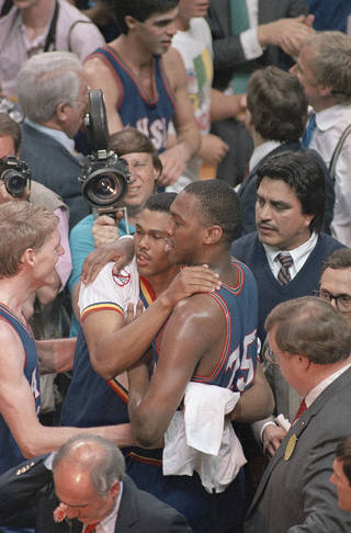 Kansas' Danny Manning, right, hugs injured teammate Archie Marshall after Manning led Kansas to a 83-79 victory over Oklahoma to win the championship of the NCAA final four tournament in Kansas City on Monday, April 5, 1988. Manning had dedicated the best his college career to Marshall after he has sidelined with a knee injury. (AP Photo/Susan Ragan) Susan Ragan - ASSOCIATED PRESS