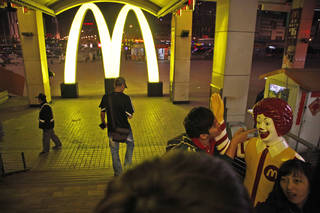 A man poses for photos with Ronald McDonald outside one of McDonald's branch at a train station in Shen yang in northern China's Liaoning province. AP Photo Ng Han Guan - AP