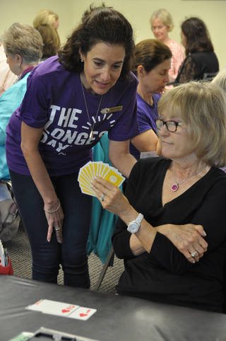 "A volunteer for ""The Longest Day"" consults a bridge player at last year's fundraising event. Photo provided"