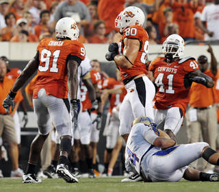 OSU's Ugo Chinasa (91), Cooper Bassett (80) and Orie Lemon (41) celebrate a sack of TU quarterback G.J. Kinne (4) by Bassett in the second quarter during the college football game between the University of Tulsa (TU) and Oklahoma State University (OSU) at Boone Pickens Stadium in Stillwater, Oklahoma, Saturday, September 18, 2010. Photo by Nate Billings, The Oklahoman